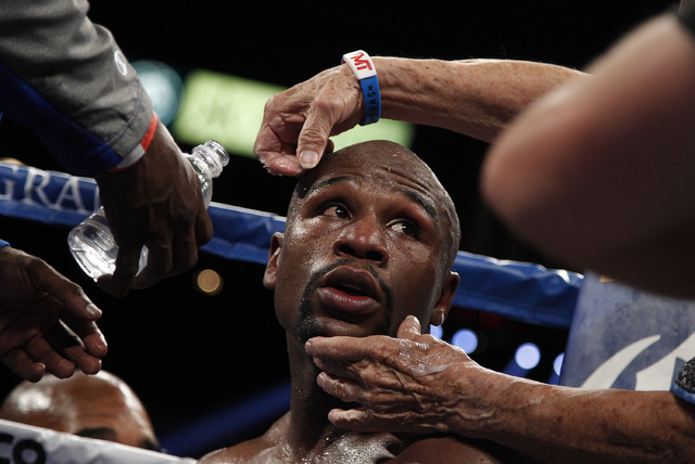 Floyd Mayweather gets worked on in his corner between rounds during his WBC and WBA super welterweight title bout at the MGM Grand in Las Vegas Saturday, Sept. 14, 2013. (John Locher/Las Vegas Rev ...