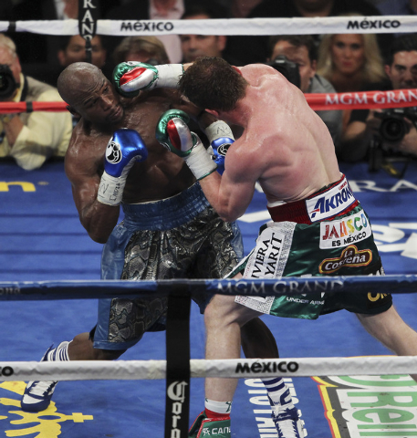 Floyd Mayweather, left, sustains a blow by Canelo Alvarez during their WBC and the WBA Super Welterweight bout at the MGM Grand Garden Arena in Las Vegas on Sept. 14, 2013. (Jason Bean/Las Vegas R ...
