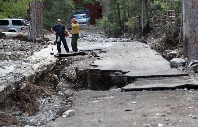 Chris Crowley, left, and Raul Arroyo, right, both of the Nevada Division of Forestry stand near the top of Rainbow Canyon Blvd. in the Rainbow Canyon subdivision in Kyle Canyon on Monday Sept. 2,  ...
