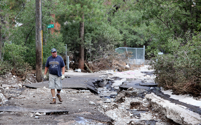 Dennis Lovell a resident of Kyle Canyon walks near the top of Rainbow Canyon Blvd. in the Rainbow Canyon subdivision in Kyle Canyon on Monday Sept. 2, 2013. The road was washed out by heavy rains  ...