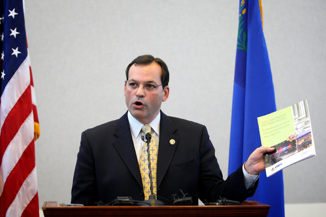 Joshua Ederheimer, U.S. Department of Justice Office of Community Oriented Policing Services office acting director, shows a copy of a six-month review of the Las Vegas Metropolitan Police Departm ...