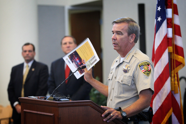 Clark County Sheriff Doug Gillespie, right, holds up a copy of a Department of Justice review of the Las Vegas Metropolitan Police Department's use of force policies and practices at a press confe ...