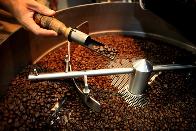 Erik Anderson, owner of Colorado River Coffee Roasters, pulls coffee beans to smell them after they were roasted at the Boulder City, Nev., business Thursday, Sep. 12, 2013. (Jessica Ebelhar/Las V ...