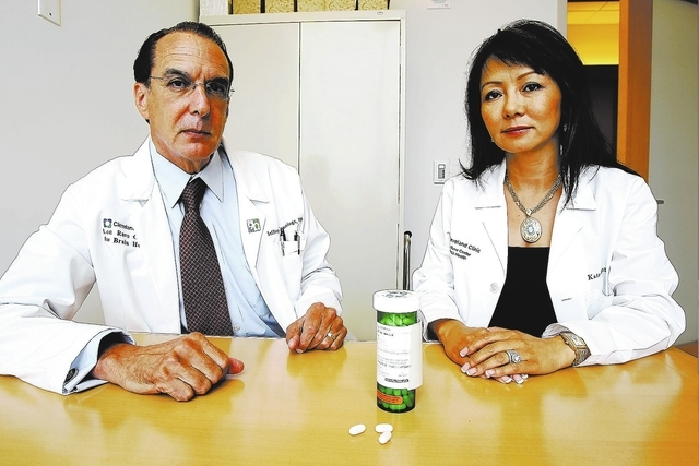 K.M. Cannon/Las Vegas Review-Journal Drs. Jeffrey Cummings, left, and Kate Zhong pose at the Lou Ruvo Center for Brain Health with bexarotene, a cancer drug now used in trials to treat patients wi ...