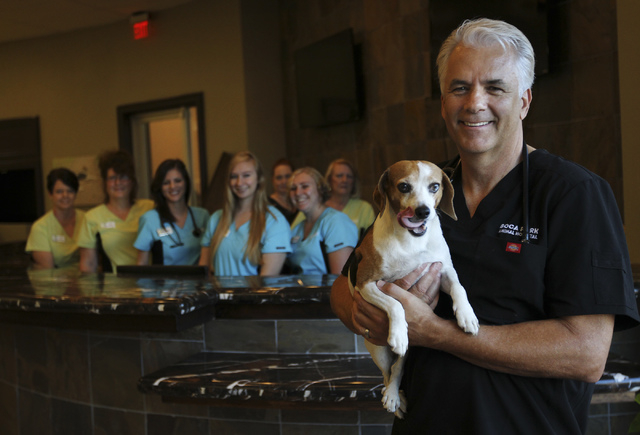 Dr. John Ensign poses for a portrait with his dog Jerome and some of his staff as he prepares to open his new Boca Park Animal Hospital on Sept. 3, 2013. (Jason Bean/Las Vegas Review-Journal)