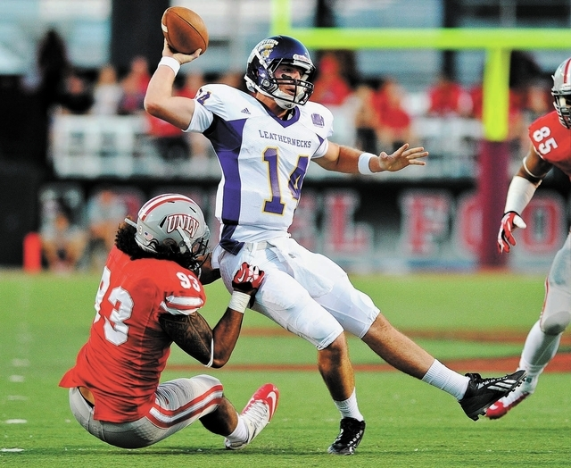 UNLV's Sonny Sanitoa (93) wraps up Western Illinois quarterback Trenton Norvell (14) during a football game at Sam Boyd Stadium in Las Vegas Saturday, Sept. 21, 2013. (David Cleveland/Las Vegas Re ...