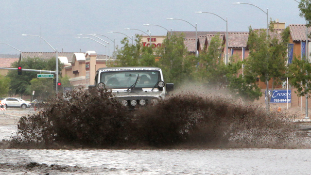 A Jeep goes drives through flood waters on Grand Teton drive in the northwest part of the valley on Monday, August 26, 2013. Flooding on Grand Teton could be alleviated with a project that could b ...
