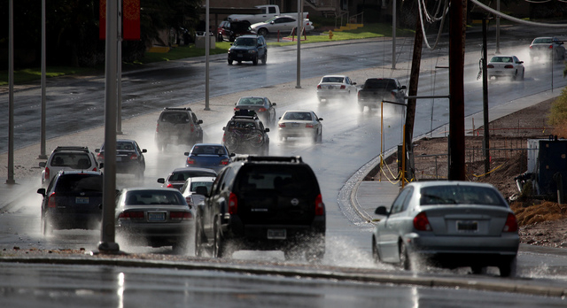 Cars drive on a flooded Sunset road near Arroyo Grande Boulevard in Henderson on Monday, Sep. 2, 2013. The road was briefly flooded from falling rain in the afternoon. (Justin Yurkanin/Las Vegas R ...