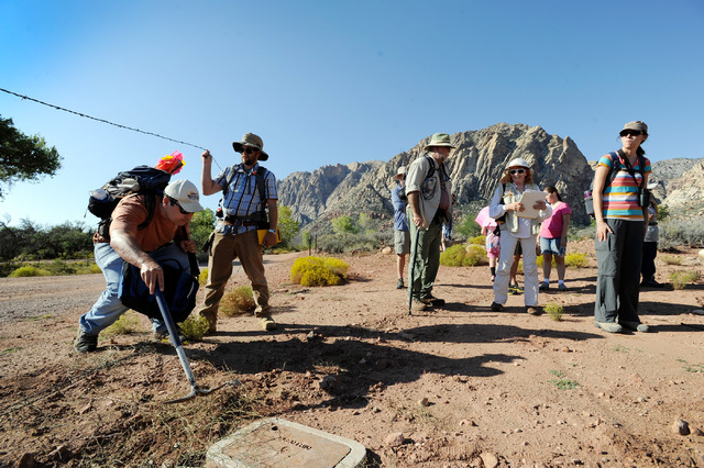 Josh Bonde, geology professor from UNLV climbs under the barb wire at Spring Mountain Ranch State Park before surveying on Saturday, Sept. 14, 2013. Bonde and several dozen students and volunteers ...