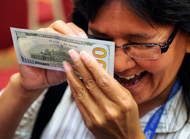 Donna Perkins from the Red Lake Gaming in Minnesota examines a new US $100. bill during G2E at the Sands Expo and Convention Center on Wednesday, Sept. 25, 2013. The newly redesigned note containi ...