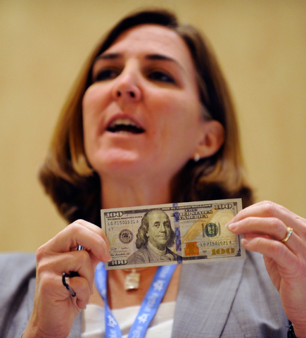 Lorelei Pagano, assistant director of the Division of Reserve Bank Operation and Payment Systems, displays a new US $100. bill during G2E at the Sands Expo and Convention Center on Wednesday, Sept ...