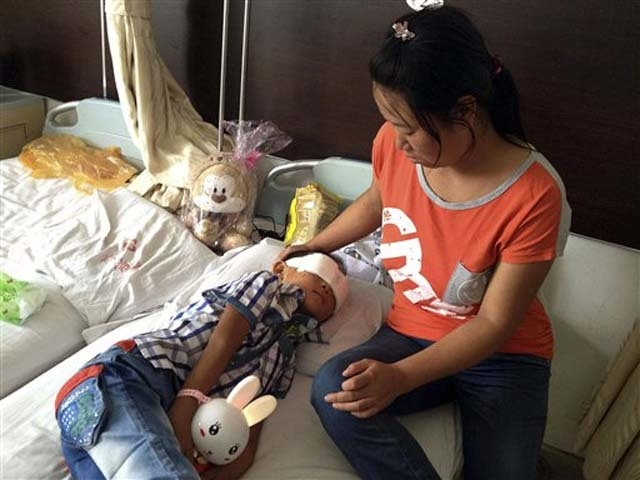 In this Aug. 28, 2013 photo, Guo Bin recuperates near his mother from an attack in the rural area of Linfen city that left him blind at a hospital in Taiyuan in northwest China's Shanxi province.  ...