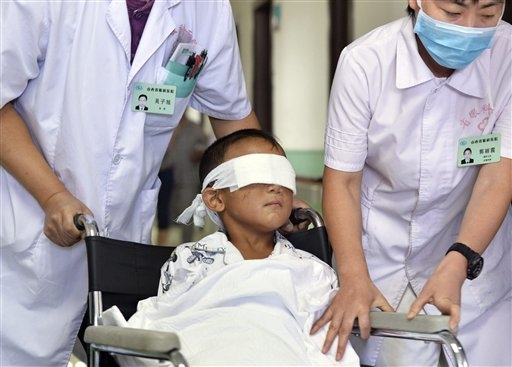 In this Aug. 30, 2013 photo, Guo Bin, 6, is pushed on a wheelchair by a doctor and a nurse at a hospital in Taiyuan, in northern China's Shanxi province. (AP Photo)