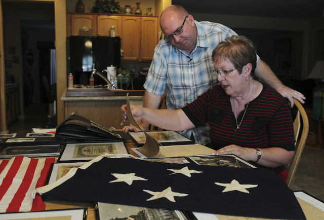 Christopher Nichols, left, grandson of Cox. Frank Orban, and Pam Nichols, daughter of Orban, look over some of the memorabilia left to them from the historic signing of the treaty that ended WWII  ...