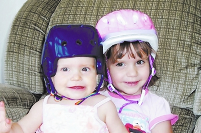 Abbey Bartko, right, dons her bike helmet in support of her little sister, Emily, who wore a helmet to help protect her from bruising caused by a rare form of hemophilia. (Courtsey photo)