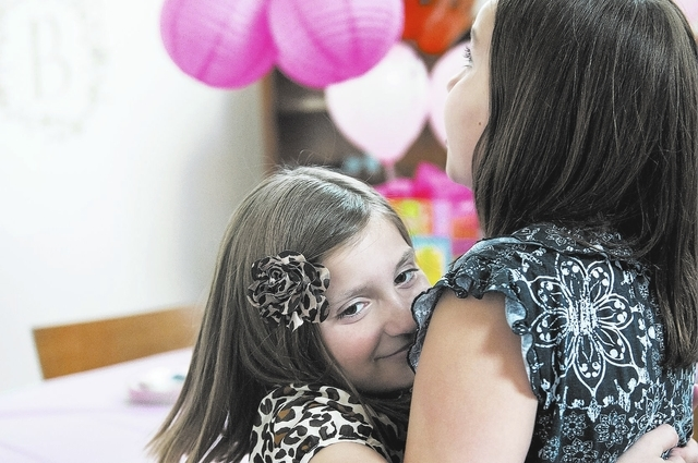 Emily Bartko, 8, embraces her older sister Abbey, 10, during her birthday party at their home, Saturday, Sept. 7, 2013, in Las Vegas, Nev. Emily and her 4-month-old brother Aaron inherited Factor  ...