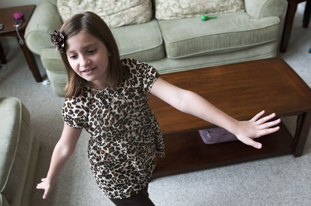 Emily Bartko, 8, dances to the rhythm of a video game song during her birthday celebration at her home, Saturday, Sept. 7, 2013, in Las Vegas, Nev. Emily and her 4-month-old brother Aaron inherite ...