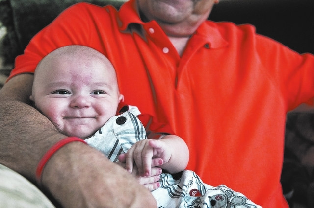Bob Bozick holds his 4-month-old grandson Aaron Bartko during a family birthday gathering at his daughter's home, Saturday, Sept. 7, 2013, in Las Vegas, Nev. Aaron and his 8-year-old sister Emily  ...