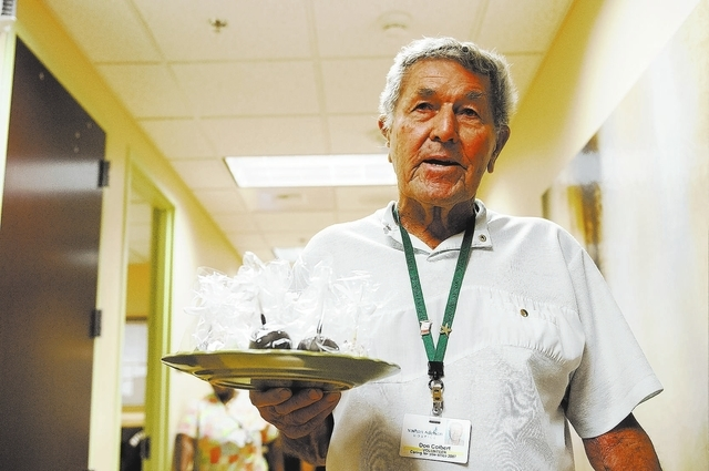 Don Colbert, volunteer at Nathan Adelson Hospice, holds a plate full of cake pops as he gets ready to deliver them to patients and family members Aug. 13. Local doctor Michael Zimmerman, who also  ...