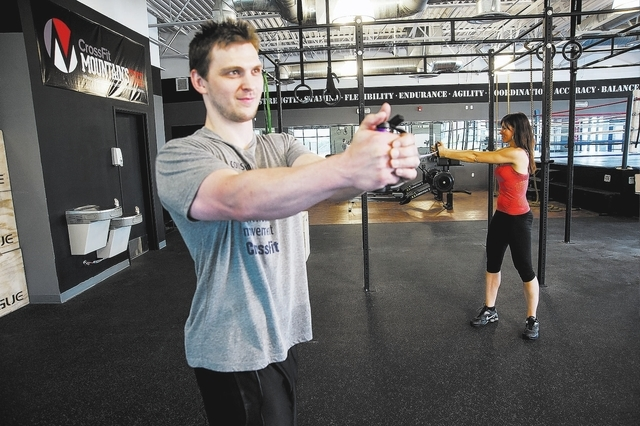 Martin s. Fuentes/the associated press Personal Trainers, from left, Chris Huth, and Laura Salcedo, of Las Vegas, demonstrates the two-person band torso rotation middle position at the Cross Fit M ...