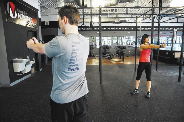 Personal Trainers, from left, Chris Huth, and Laura Salcedo, of Las Vegas, demonstrates the two-person band torso rotation finishing position at the Cross Fit Mountains Edge gym, in Las Vegas, Wed ...