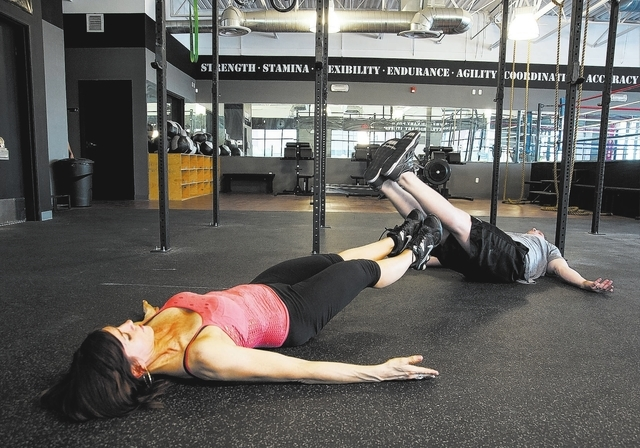 Personal Trainers, from left, Laura Salcedo, and Chris Huth of Las Vegas, demonstrates the two-person leg circles by rotating their legs around the others legs at the Cross Fit Mountains Edge gym, ...