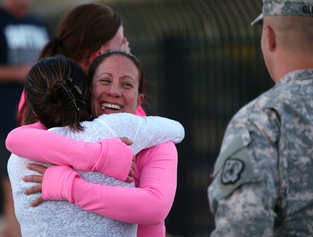 Event organizer Laura Boldry, center, hugs Tracy Kelly after completing a memorial 5K walk and run in honor of the victims of the 2011 IHOP shooting in Carson City, Nev., on Friday, Sept. 6, 2013. ...