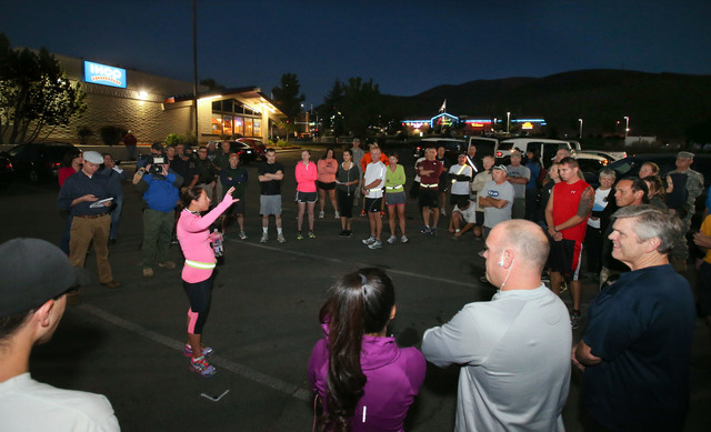 Event organizer Laura Boldry, center, talks to participants before an early morning memorial 5K walk and run in honor of the victims of the 2011 IHOP shooting in Carson City, Nev., on Friday, Sept ...