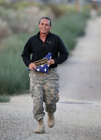Retired Nevada National Guard Maj. Ken Curtzwiler runs in a memorial 5K walk and run in honor of the victims of the 2011 IHOP shooting in Carson City, Nev., on Friday, Sept. 6, 2013.  Curtzwiler's ...