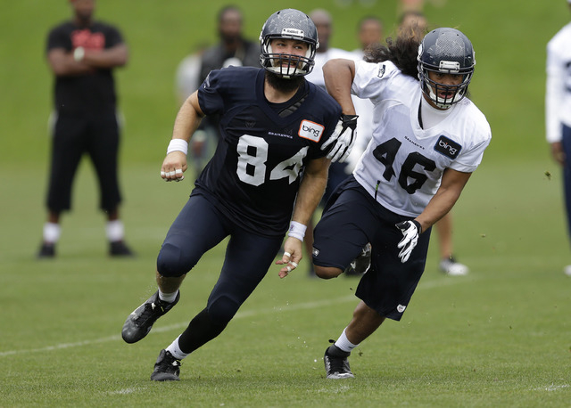 Seattle Seahawks linebacker John Lotulelei (46) is blocked by tight end Sean McGrath (84) during NFL football training camp in Renton, Wash. (AP Photo/Ted S. Warren)