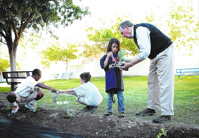 Dr. Roy Glover, right, medical director for BODIESɔhe Exhibition, helps six-year-old Dennisse Gonzalez in planting an artichoke plant in a new garden at the Boys & Girls Club Donald W. Reynolds C ...