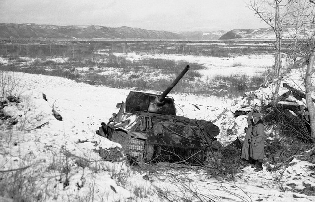 Chaplain B.L. Hickey, left, of Rochester and Waverly, N.Y., the Catholic chaplain for 5th Regiment, Marines, and Sgt. E.E. Buhman of St. Louis look over a T-34 Chinese tank in the Chosin Reservoir ...