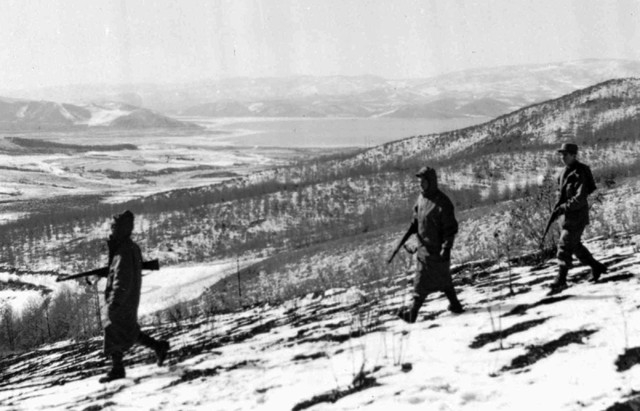 Marines keep rifles handy as they patrol in the icy hills near North Korea's Chosin Reservoir, which is visible in background, on Nov. 27, 1950. (AP Photo/Frank Noels)