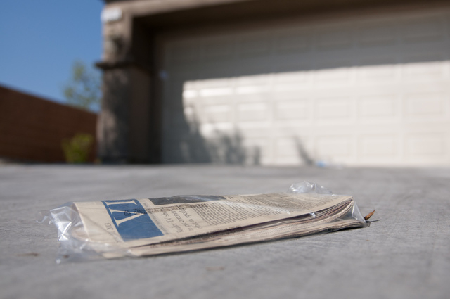 An old newspaper sits on the driveway at the home where the bodies of Megan Kathleen Lanza and Nicholas Frank Lanza were found Wednesday in Las Vegas, Nev., Friday, Sept.13, 2013. (Erik Verduzco/L ...