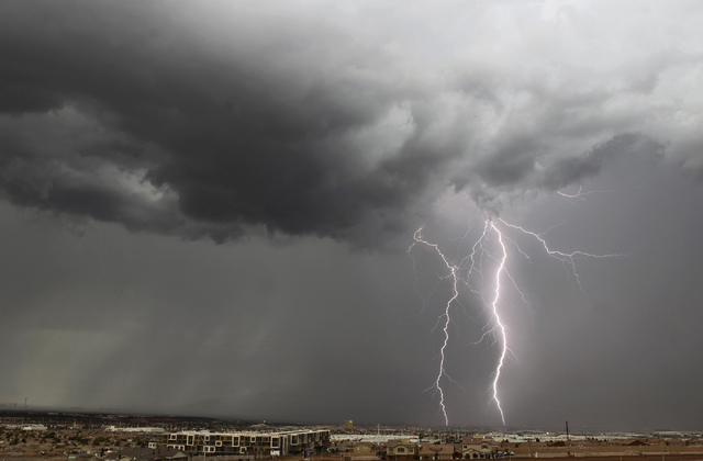 Lightning strikes touch the ground in Henderson, as seen looking north from Gibson Road and U.S. Route 95, as a thunder storm rolls over the Las Vegas Valley on Wednesday, Sept. 11, 2013. (Jason B ...