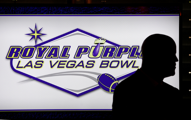 A person stands in front of a screen showing the newly announced sponsor of the Las Vegas Bowl at a luncheon in Las Vegas Wednesday, Sept. 25, 2013.  (John Locher/Las Vegas Review-Journal)