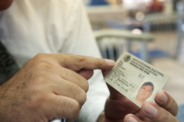Fermin Ramirez, a volunteer coordinator for Mexico Presente in Nevada, shows his Mexican electoral card during a party meeting, Wednesday, Aug. 21, 2013, in Las Vegas, Nev. Mexico Presente is an i ...