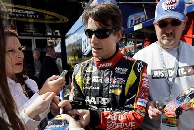 Nam Y. Huh/The Associated Press Driver Jeff Gordon signs autographs for fans as he walks to his garage during practice for Sunday's NASCAR Sprint Cup Series auto race at Chicagoland Speedway in Jo ...