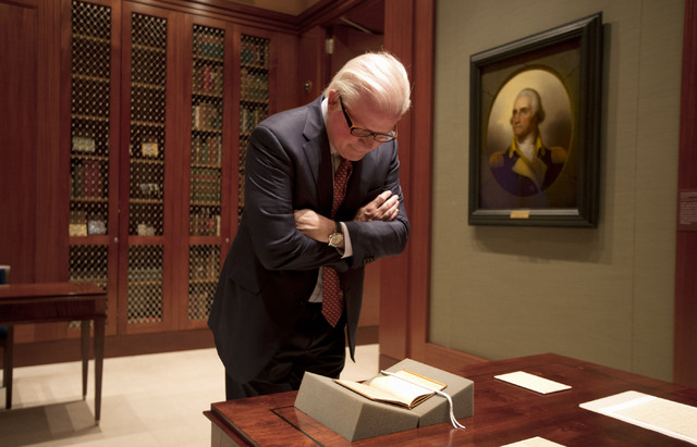 This photo taken Tuesday, Sept. 24, 2013 shows Curt Viebranz, president and CEO of George Washington's Mount Vernon Estate, Museum, and Gardens, looking at a book that belonged to George Washingto ...