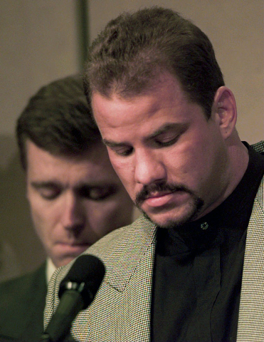 FILE - In this Feb. 15, 1996 file photo, heavyweight boxer Tommy Morrison, right, and promoter Tony Holden bow their heads during an emotional moment at a news conference about Morrison being HIV  ...