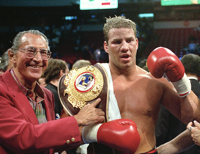 FILE - In this June 7, 1993 file photo, newly crowned WBO heavyweight champion Tommy Morrison receives his championship belt after defeating George Foreman in Las Vegas, Nev. Morrison, a former he ...
