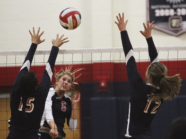 Coronado's Taylor Jackson (5) spikes the past Legacy's Saipeti Fuiava (15) and Reina Martin (12) during their volleyball match in Henderson on Sept. 17, 2013. (Jason Bean/Las Vegas Review-Journal)