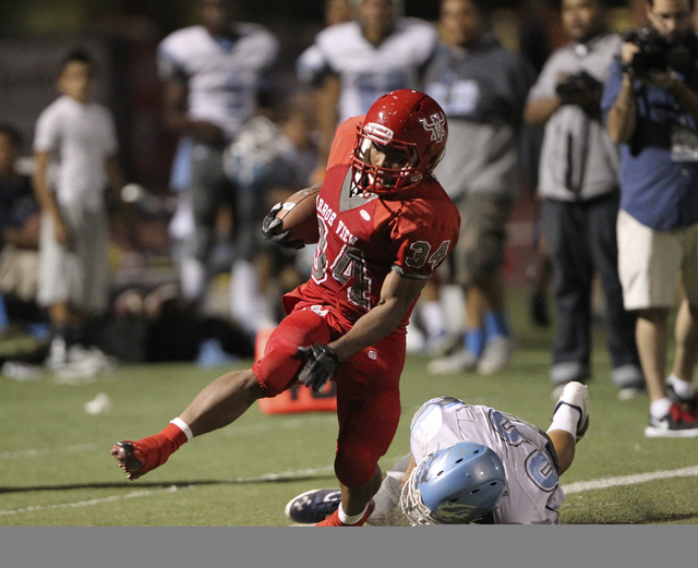 Arbor View running back Herman Gray tries to avoid a tackle by Centennial defensive back Samuel Liaga during a 47-yard run in the second quarter of their football game at Arbor View High School Th ...