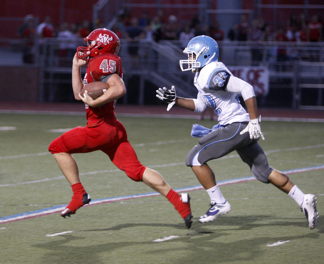 Arbor View running back Ricky Clark runs ahead of Centennial defensive back Samuel Liaga for 73-yard gain on the first play from scrimmage against Centennial during their football game at Arbor Vi ...