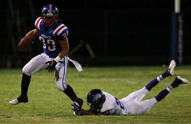 Liberty's Brenan Adams (33) jumps past Silverado's Daniel Savage (21) during a football game at Liberty High School in Henderson on Saturday, Sept. 7, 2013. Liberty won 35-8 against Silverado. (Ch ...