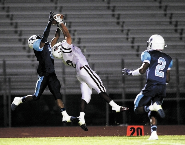 Canyon Springs' A.J. Cooper (3) breaks up a pass intended for Desert Oasis' Gary Abdella (2) during their football game in North Las Vegas on Sept. 27, 2013. (Jason Bean/Las Vegas Review-Journal)