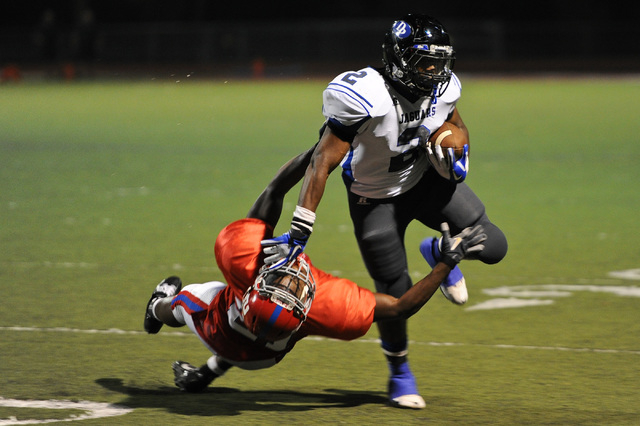 Desert Pines running back Eric Wilkes (2) stiff arms Valley defender Malik Batiste (21) during a football game at Valley High School in Las Vegas Thursday, Sep. 12, 2013. (David Cleveland/Las Vega ...