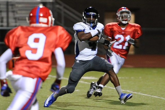 Desert Pines Tim Hough (4) cuts through Valley defenders Iyen Medlock (9) and Malik Batiste (21) in route to a 32-yard touchdown score during a football game at Valley High School in Las Vegas Thu ...