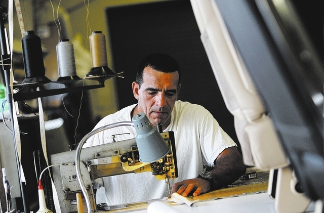 An inmate worker sews together a piece of custom interior upholstery while participating in the car restoration program, operated through Silver State Industries, at the Southern Desert Correction ...