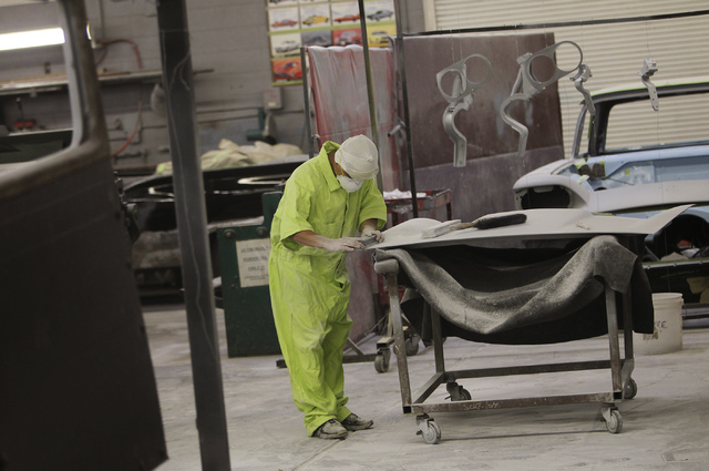 An inmate worker sands a hood panel while participating in the car restoration program, operated through Silver State Industries, at the Southern Desert Correctional Center near Indian Springs on  ...